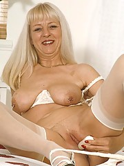 Blonde granny stroking her wet pussy in the bedroom