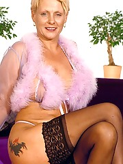 Hot granny Belinda is loving her furry robe and flaunting her sexy thongs and sheer back stockings